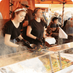 Two women serving street food to tourists during a food tour