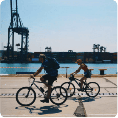 Two tourists riding bicicles on a port area during a bike tour