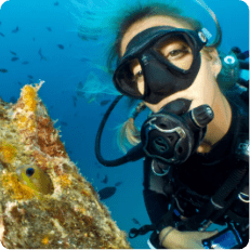 Tourist poses next to a coral during a snorkeling tour