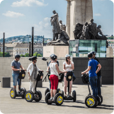 Group of tourists riding segways next to a monument listening to the tour guide