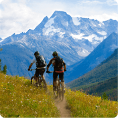 Two tourists riding bicycles on a green field during a mountain bike tour