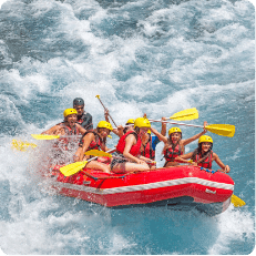A group of tourists going down river rapids during a river rafting tour
