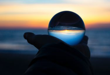 Tourism rebound predictions. Hand holding a crystal ball.