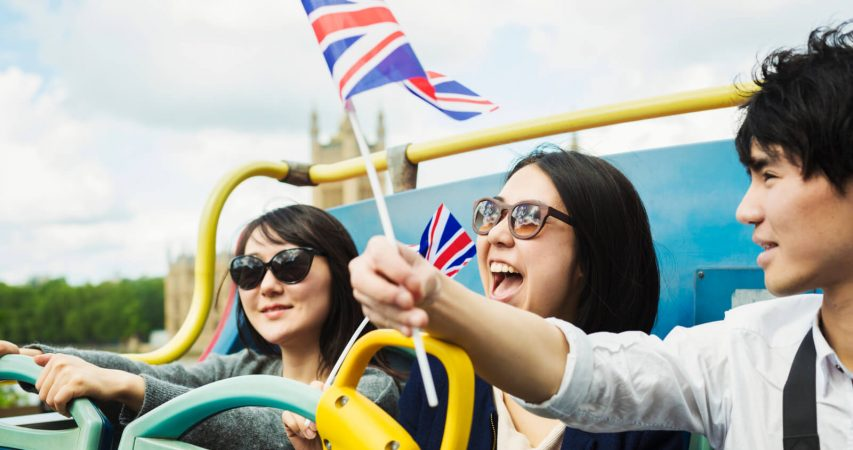 Facebook cover image of three tourists waiving the UK flag during a tour