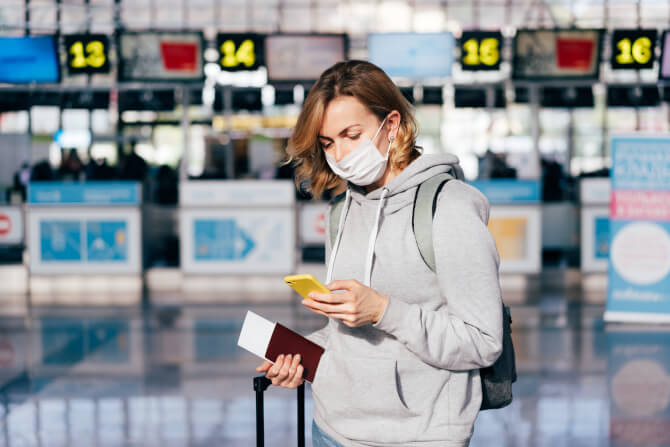 a woman in a protective medical mask at the airport travel search trends