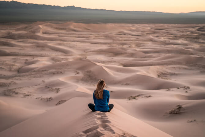 woman meditating desert starting a tour operator business