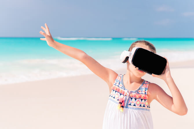 kid wearing virtual reality glasses on beach smart destinations